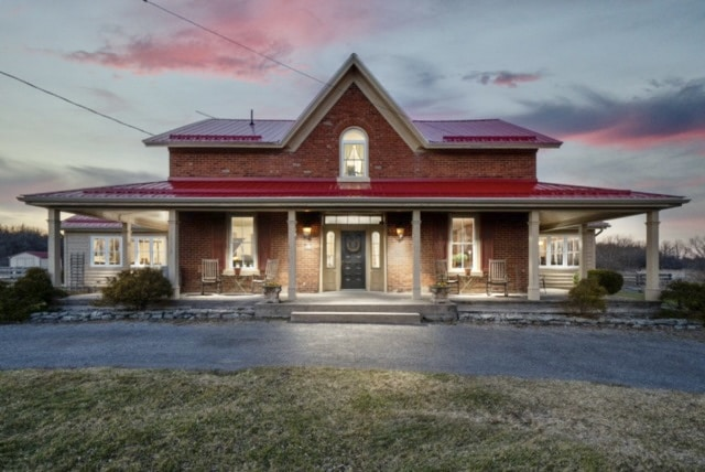 Red roofed farmhouse, dusk, lit from the inside. Classic Prince Edward County farmhouse.
