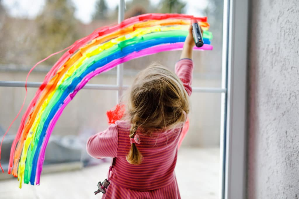 A little girl pasting a rainbow on a window for Reaching For Rainbows girls' charity in picton, prince edward county